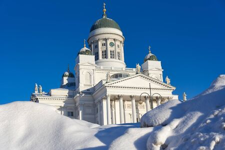 Helsinki, Finland - February 6, 2019: Helsinki Cathedral behind huge pile of snow on a sunny and cold winter afternoon after weeks of heavy snowfall Standard-Bild - 138483937