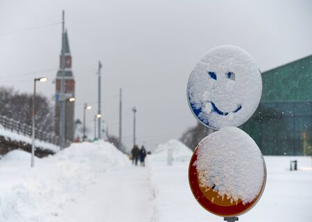 Snowy traffic sign with a smiling face drawn into snow in the center of Helsinki, Finland Standard-Bild - 139797828