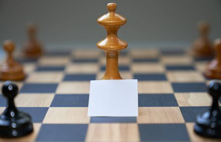 Concept chess pieces express social distancing with blank white board in front of the center piece.