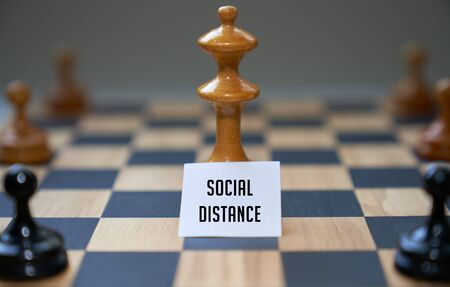 Concept chess pieces express social distancing with white board and text social distance in front of the center piece on the chess board.