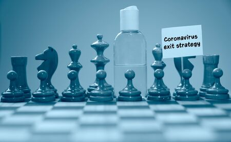 Coronavirus concept image chess pieces and hand sanitizer on chessboard illustrating global struggle against novel covid-19 outbreak with coronavirus exit strategy sign.