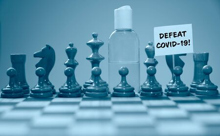 Coronavirus concept image chess pieces and hand sanitizer on chessboard illustrating global struggle against novel covid-19 outbreak with defeat covid-19 sign. 免版税图像