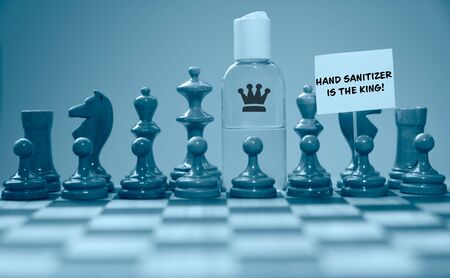 Coronavirus concept image chess pieces and hand sanitizer on chessboard illustrating global struggle against novel covid-19 outbreak with hand sanitizer is the king sign.