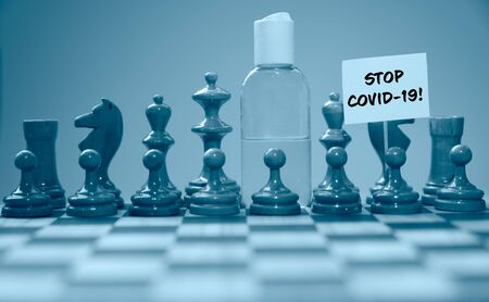 Coronavirus concept image chess pieces and hand sanitizer on chessboard illustrating global struggle against novel covid-19 outbreak with stop covid-19 sign.