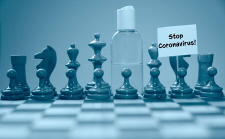 Coronavirus concept image chess pieces and hand sanitizer on chessboard illustrating global struggle against novel covid-19 outbreak with stop coronavirus sign.