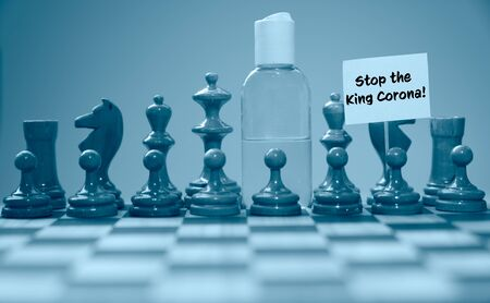 Coronavirus concept image chess pieces and hand sanitizer on chessboard illustrating global struggle against novel covid-19 outbreak with Stop the King   sign. Standard-Bild