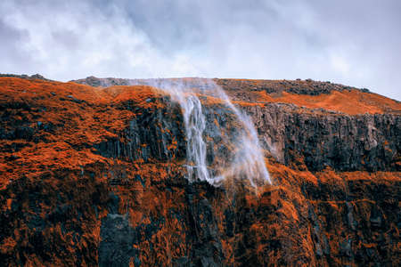 Dramatic scne of water from waterfall being blown away by strong and gusty storm winds off the steep cliff located in nearby Seljalandsfoss in Southern Iceland. Here photographed in early October 2019.
