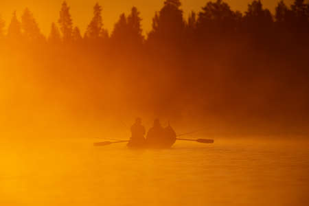 Salmon fishing with rowboat at the sunrise light on misty morning in the Tornio river in Finnish Lapland in June 2020.