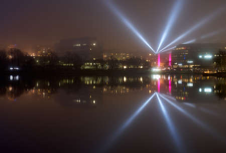 Helsinki, Finland - January 6, 2020: Light beams from light installation Lyyra in Kallion virastotalo building reflected from the Baltic sea in Hakaniemi district of Helsinki during Lux Helsinki 2020 light arts festival on extremely thick fog weather cond