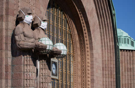 Helsinki, Finland - 16 August 2020: Iconic stone men statues by the side of the entrance to the Helsinki Central Railway Station decorated as wearing coronavirus protective masks provided by government-owned railway company VR.