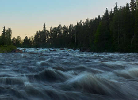 Kengis rapids on Torne river in Northern Sweden near border with Finland with midnight sun in early morning in July 2019. Standard-Bild