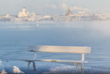 Traditional wooden and frosty resting bench in Helsinki, Finland  on extremely cold winter morning with freezing Baltic Sea and downtown Helsinki skyline on the background.