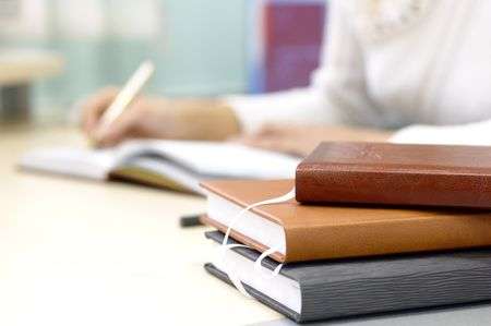 business writing: books for notes on a table with somebody hand writing Stock Photo