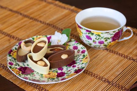 le thé vert et le lait et bonbons de chocolat noir sur la toile Banque d'images