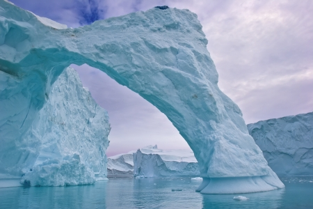 an ice arch carved by the wind in a giant iceberg, greenland photo