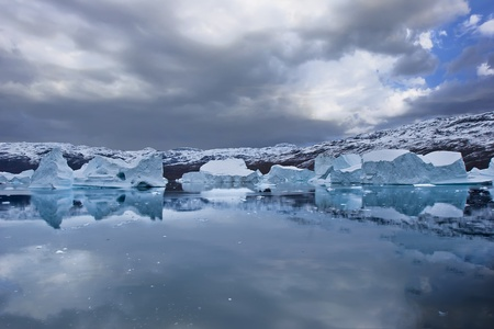 the coasts of greenland with giant floating icebergs and mountains photo