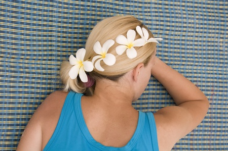 Woman lying on the beach with flowers in her hair on Thailand Stock Photo - 8755482