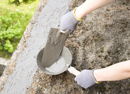 Close-up of womans hand holding a trowel, applying mortar  photo