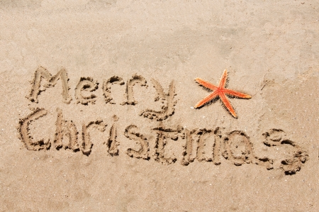 Merry Christmas written in the sand with star photo