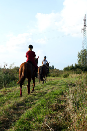 Two young girls horseback riding in nature.