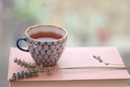 Tea in a vintage porcelain cup, with lavender and old book. Shallow depth of field and soft focus.