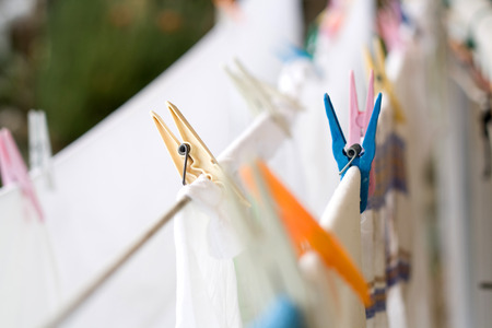 clothes clips: Multicolored clothes clips on the wire, selective focus. Stock Photo