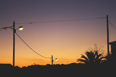 Street lamps, power lines, houses and trees. Black silhouettes on colorful background, photographed during sunset.