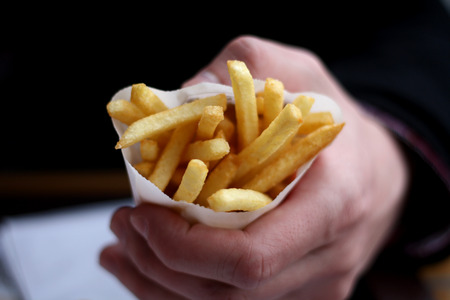 frites: Hand holding small portion of French fries.
