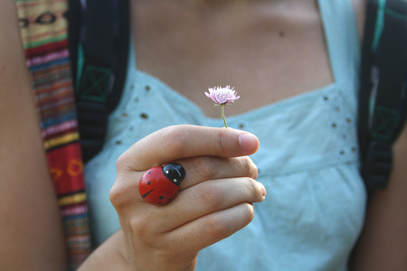 Female hiker holding a small flower, hand detail. Enjoying nature and spring concept. Archivio Fotografico