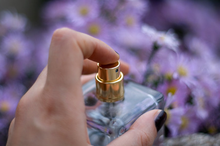 eau: Hand holding perfume bottle, flower bokeh and selective focus.