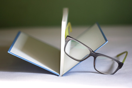 Eyeglasses and open book on the bed. Selective focus. photo