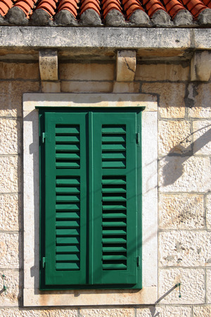 mediterranean house: Architectural detail on a traditional mediterranean house: green window on a stone facade. Stock Photo