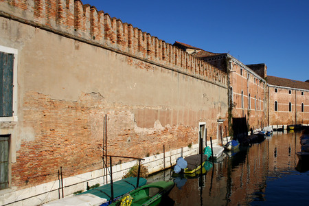 arsenal: Industrial brick building near the canal in The Venetian Arsenal. Canal is filled with small boats.