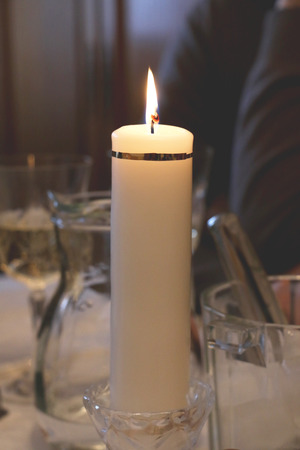 lighted: Lighted candle on a table, table setting decoration. Darker, gloomy colors in the background. Vertical format and selective focus.