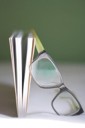 paperback: Libro e vita bassa occhiali sdraiato sul letto. Formato verticale e messa a fuoco selettiva.
