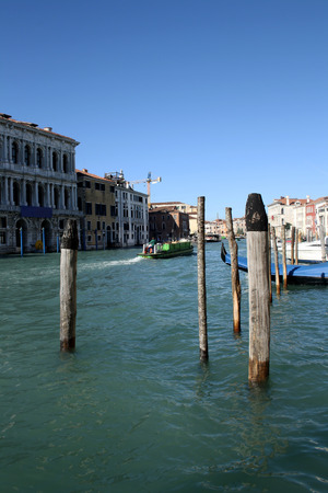 canal houses: Wooden sticks in the canal, houses and boats in the background. In Venice, Italy.