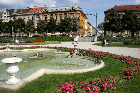 Zagreb, Croatia - September 14, 2010: People and pigeons enjoying sunny day in park Zrinjevac in Zagreb, Croatia. Editorial