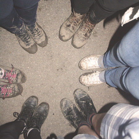 muddy: Circle of young people with dirty muddy shoes, after dancing at the music festival.