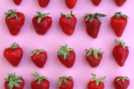 arranged: Strawberries arranged on a pink background.