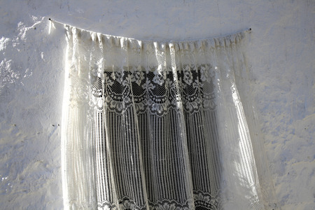 lacey: White lace curtain on a rustic white wall - typical detail on a mediterranean house.