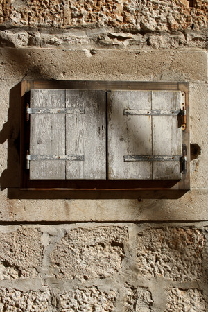 architectural  detail: Architectural detail: small rustic window on a traditional Mediterranean house. Vertical format, natural light. Stock Photo