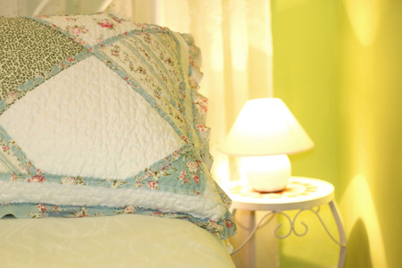 pillow case: Romantic pillow in a shabby chic bedroom with green walls. Close-up, selective focus. Stock Photo