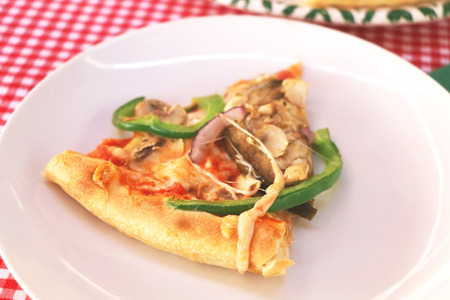 Slice of vegetarian pizza on a plate, in traditional pizzeria. Selective focus. photo