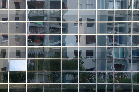 Building reflection distorted on a glass facade.