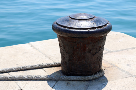 seafront: Rusty mooring bollard on a dock with nautical rope. Bright blue sea in the background.