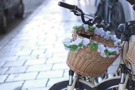 decorated bike: Bike basket decorated with flowers on the street. Selective focus.