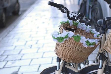 decorated bike: Cestino della bici decorato con fiori per la strada. Messa a fuoco selettiva.