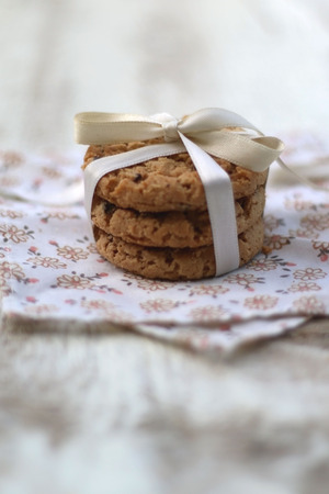 mo�o blanco: Three chocolate chip cookies with white bow and floral napkin. Rustic white background, selective focus.