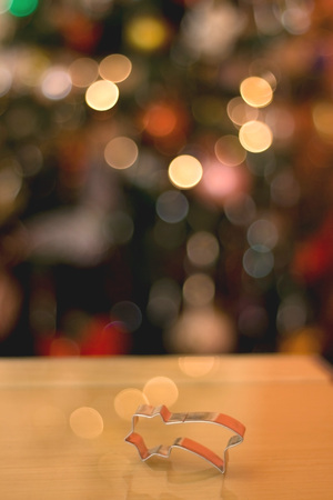 cookie cutter: Christmas cookie cutter shaped like falling star. Beautiful colorful bokeh in the background. Stock Photo