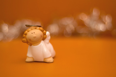 sparkly: Little figurine shaped like an angel. Orange background and sparkly bokeh. Stock Photo